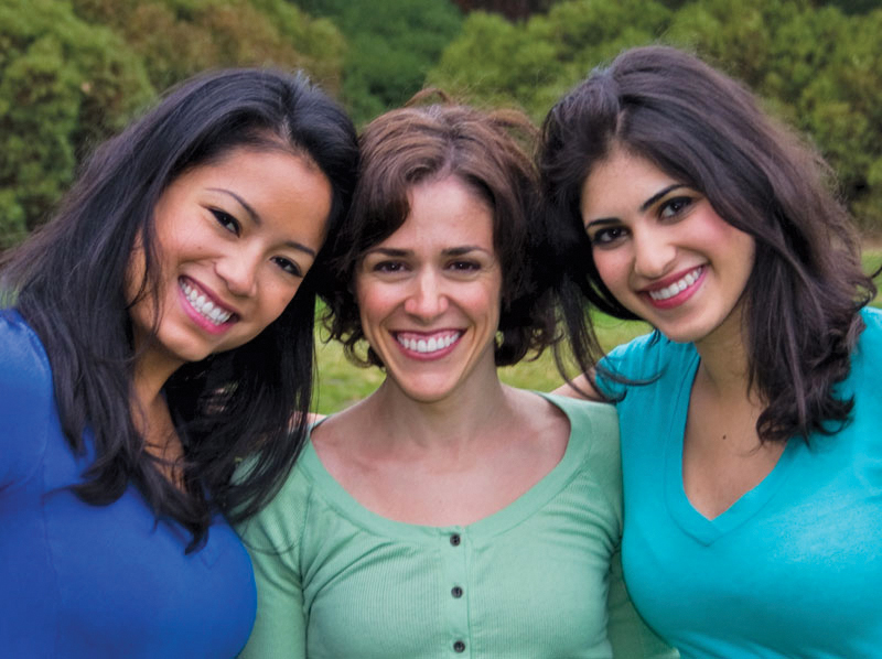 Three lady friends smiling outside.